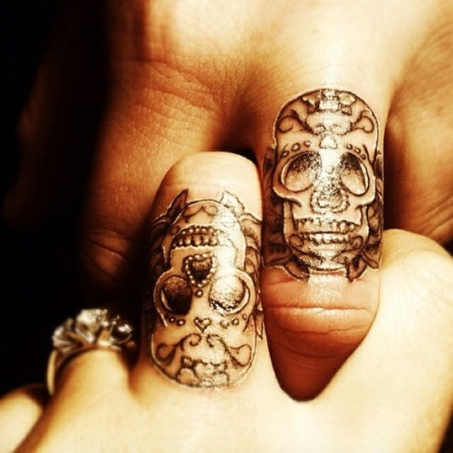Minimal skull finger tattoo
