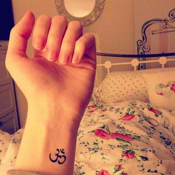 Minimal OM sign wrist tat