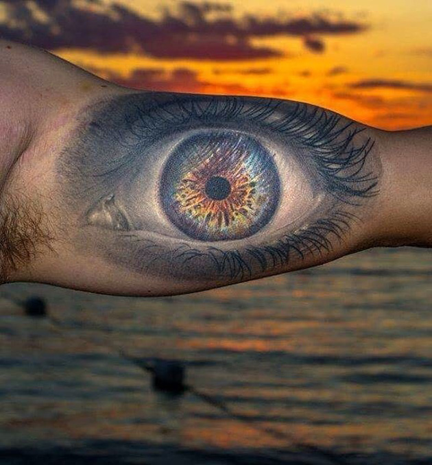 Realistic eye mens bicep tattoo