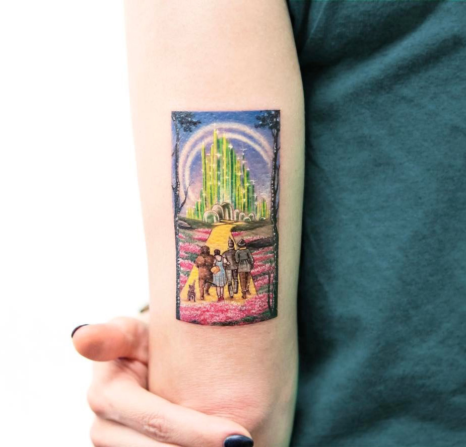 The wizard of oz miniature tattoo on girl 39 s upper arm for Best tattoo artists in nyc 2017