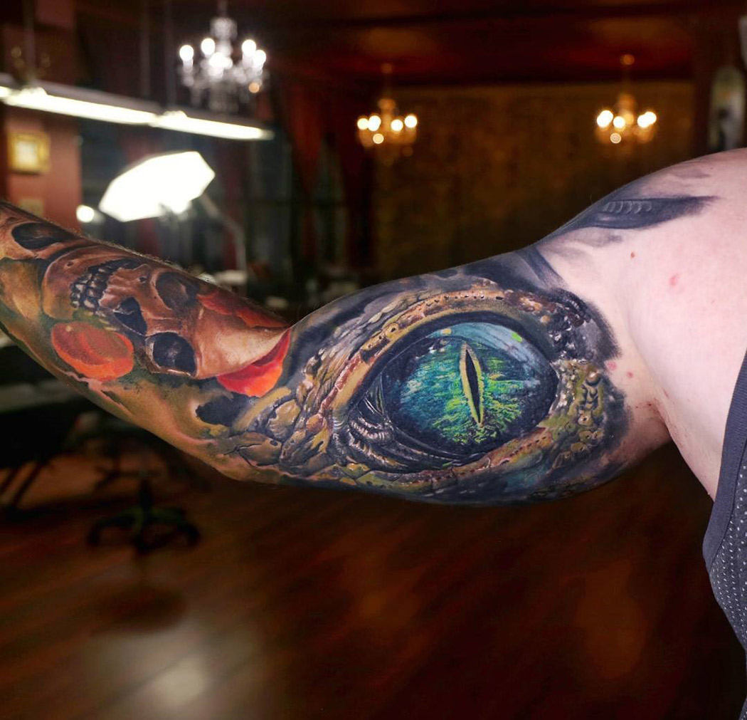 Crocodile eye bicep tattoo