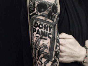 Skeleton reading Don't Panic